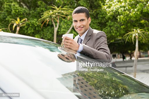 Portrait of mid adult man with coffee cup leaning on car : Stockfoto