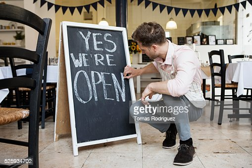 Portrait of mid adult waiter crouching by blackboard and writing : Stock-Foto