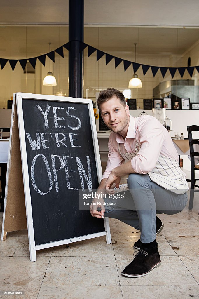 Portrait of mid adult waiter crouching by blackboard open sign : Stockfoto