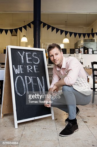 Portrait of mid adult waiter crouching by blackboard open sign : Stockfoto