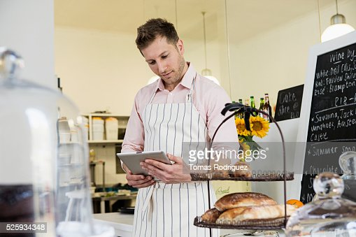 Portrait of mid adult waiter holding digital tablet behind bar counter : Stock Photo