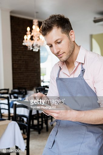 Portrait of mid adult waiter holding digital tablet : Stock-Foto