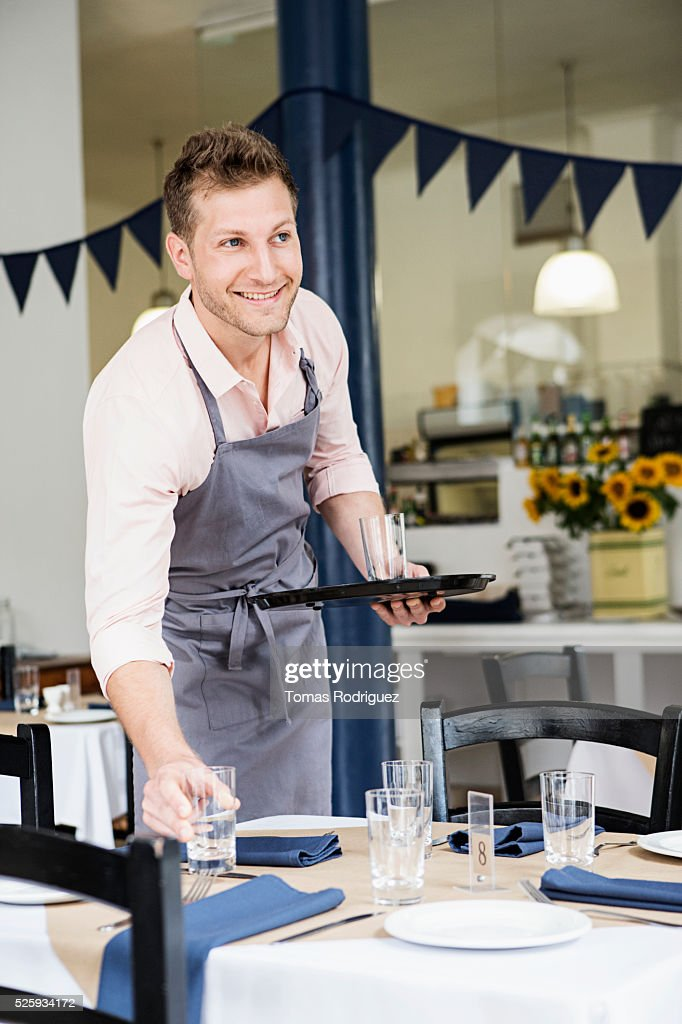 Portrait of mid adult waiter setting table at restaurant : Stock Photo