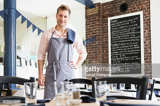 Portrait of mid adult waiter standing by table at restaurant : Stock Photo