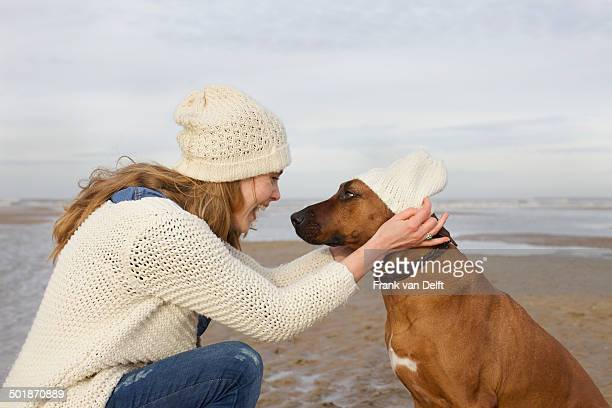 Portrait of mid adult woman and dog on beach, Bloemendaal aan Zee, Netherlands
