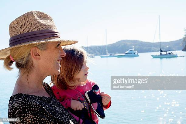 Portrait of mid adult woman and toddler daughter at coast, New Zealand