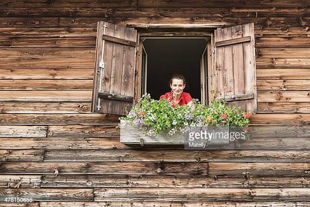 Portrait of mid adult woman at chalet window, Achenkirch,  Tyrol, Austria