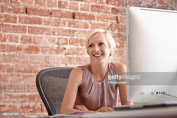 Portrait of mid adult woman at desk with brick wall