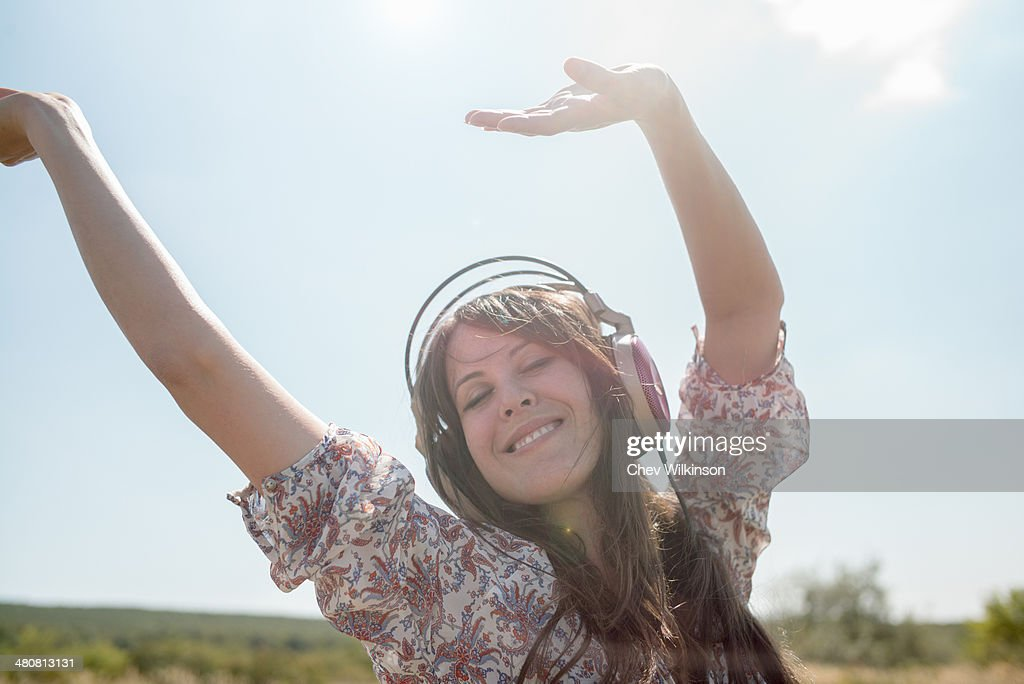 Portrait of mid adult woman dancing in field wearing headphones with arms raised