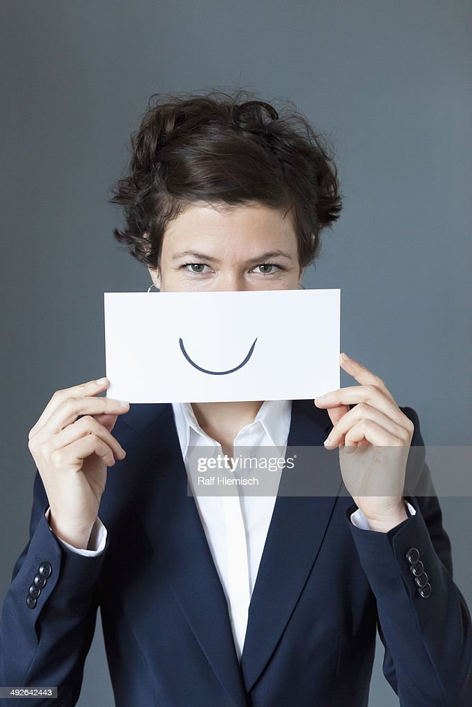 Portrait of mid adult woman holding paper with curve sign, close-up