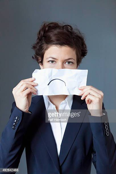 Portrait of mid adult woman holding paper with frown, close-up