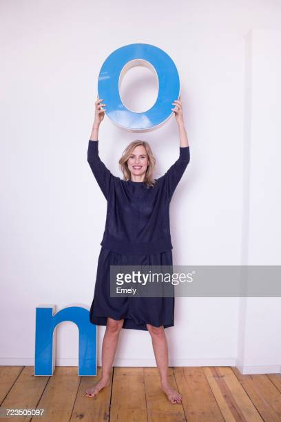 Portrait of mid adult woman, holding three-dimensional letter O, next to letter N on floor
