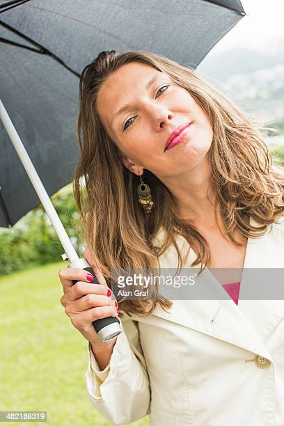 Portrait of mid adult woman holding up umbrella