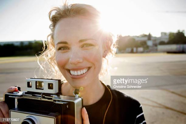 Portrait of mid adult woman in sunlight with vintage camera