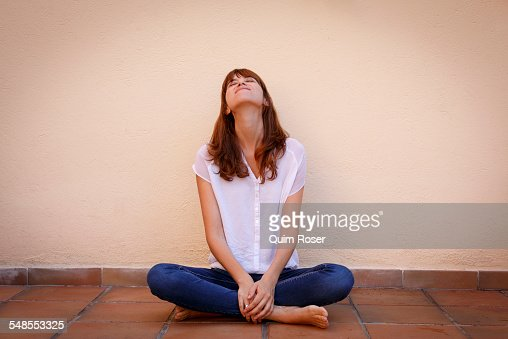 Portrait of mid adult woman in yoga pose on kitchen floor for Floor yoga poses