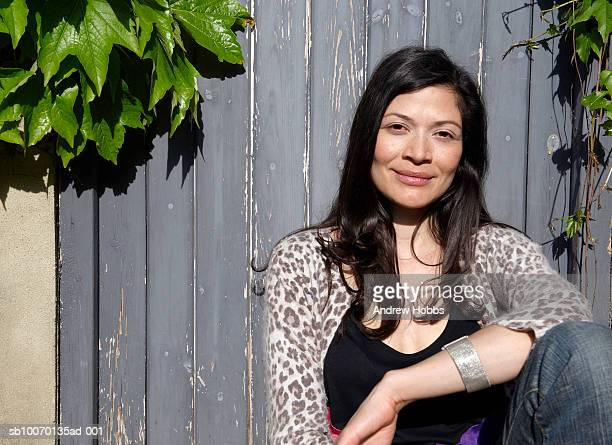 Portrait of mid adult woman leaning against fence