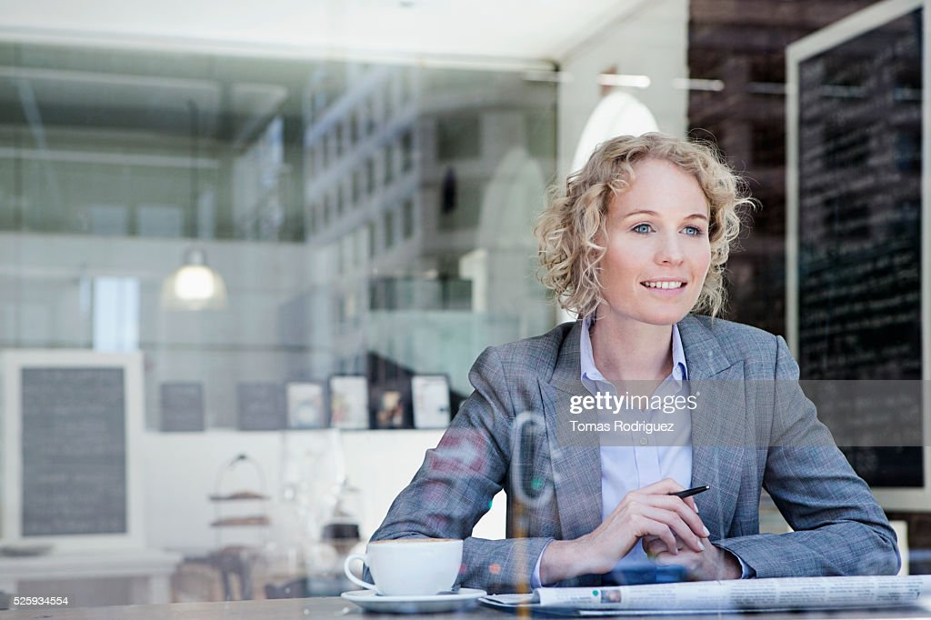 Portrait of mid adult woman relaxing in coffee shop : Stock Photo