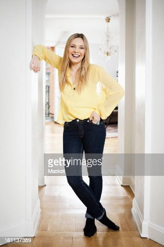Portrait of mid adult woman standing in doorway at home