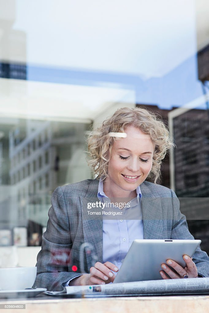 Portrait of mid adult woman using digital tablet in cafe : Stock Photo