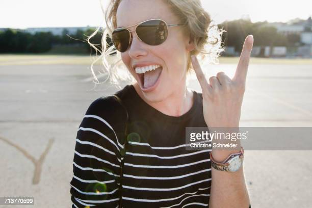 Portrait of mid adult woman wearing sunglasses making I love you hand gesture