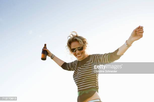 Portrait of mid adult woman with arms open against sunlit blue sky