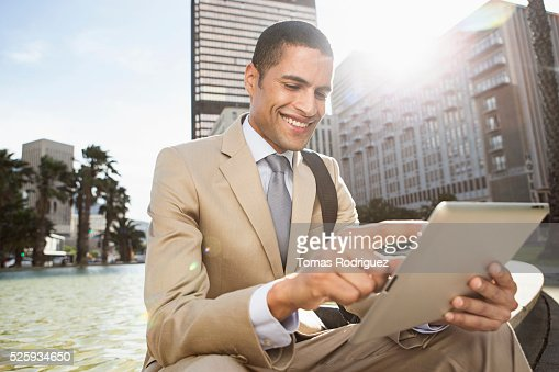 Portrait of mid man sitting by fountain and using digital tablet : Foto stock