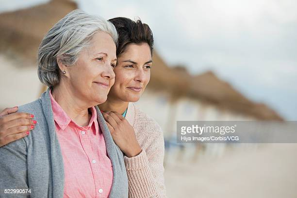 Portrait of mid-adult woman embracing senior mother on beach