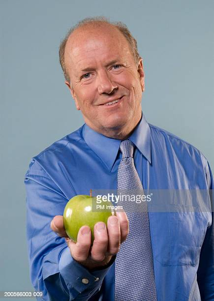 Portrait of middle aged businessman holding apple and smiling, upper half
