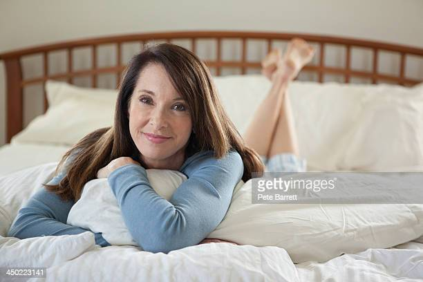 Portrait of middle aged woman laying in bed