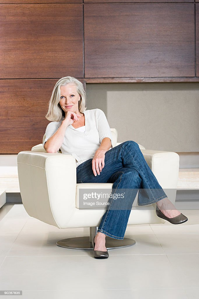 Portrait of middle aged woman sitting on modern armchair