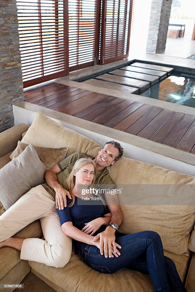 Portrait of middle-aged couple reclining on sofa : ストックフォト