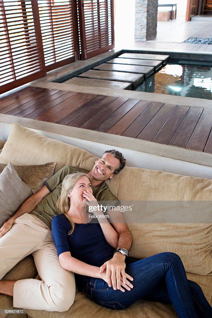 Portrait of middle-aged couple reclining on sofa : Stockfoto