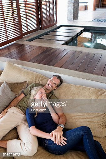 Portrait of middle-aged couple reclining on sofa : Stock Photo