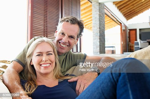 Portrait of middle-aged couple sitting on sofa : Stock Photo