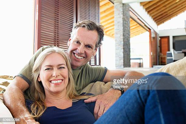 Portrait of middle-aged couple sitting on sofa
