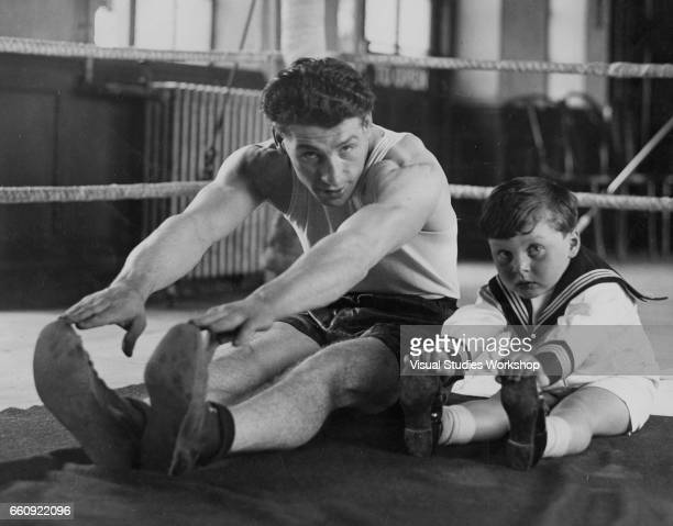 Portrait of middlewieght boxer Len Harvey as he stretches with his son during a training session London England June 18 1932