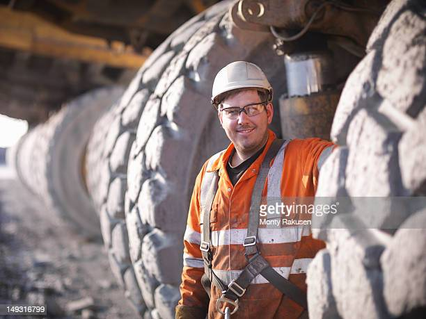 Portrait of miner standing next to  dumper truck tyres in opencast coalmine