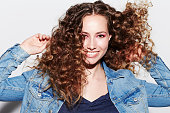 Portrait of model with curly hair, smiling