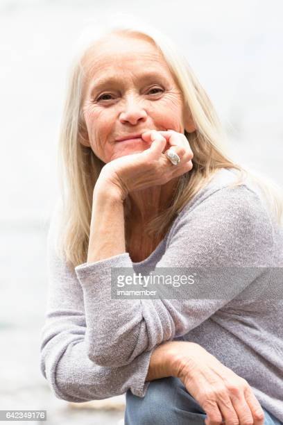 Portrait of modern attractive mature woman with hand on chin