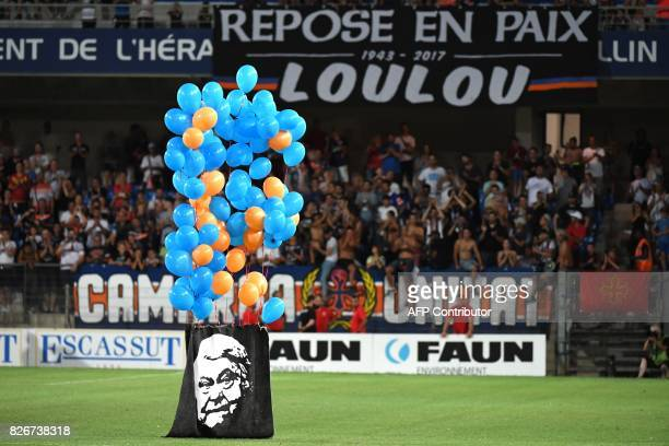 A portrait of Montpellier's late president Louis Nicollin hangs from balloons over the pitch after the French L1 football match between MHSC...