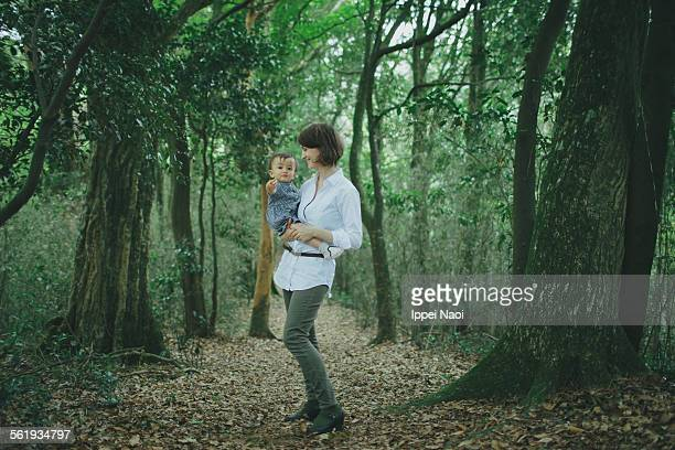 Portrait of mother and baby girl in forest