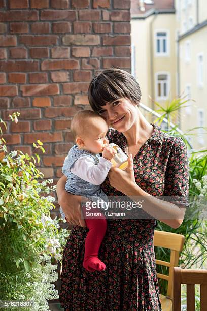 Portrait of mother and baby girl on balcony.