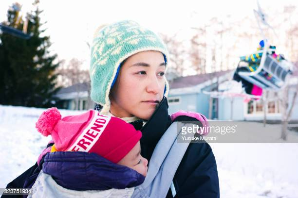Portrait of mother and daughter embracing in ski area