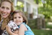 Portrait of mother and daughter (6-7 years) hugging in front of house
