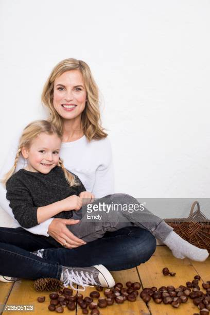 Portrait of mother and daughter, sitting on floor, surrounded by conkers and pine cones