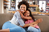 Portrait Of Mother And Daughter Sitting On Sofa Laughing