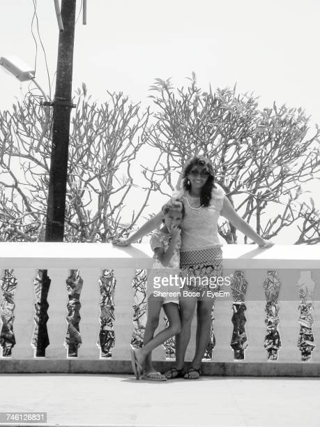 Portrait Of Mother And Daughter Standing By Railing