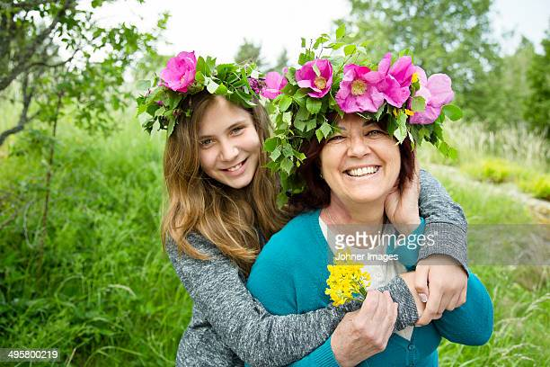 Portrait of mother and daughter wearing wreaths of flowers, Nykoping, Sodermanland, Sweden