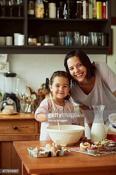 Portrait of mother and daughter while baking