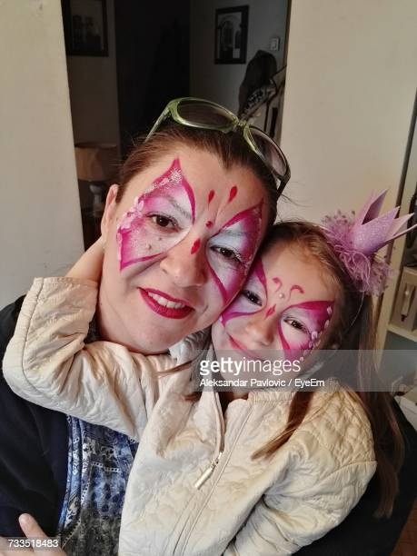 Portrait Of Mother And Daughter With Face Paint At Home